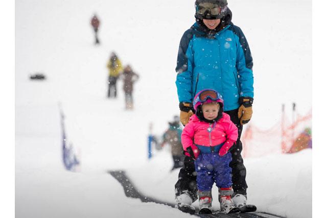 mom and daughter riding the magic carpet ski showdown montana