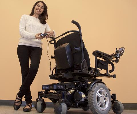 Photo of Pooja Viswanathan, co-founder and CEO of Braze Mobility standing beside a power wheelchair with the Braze Sentina installed