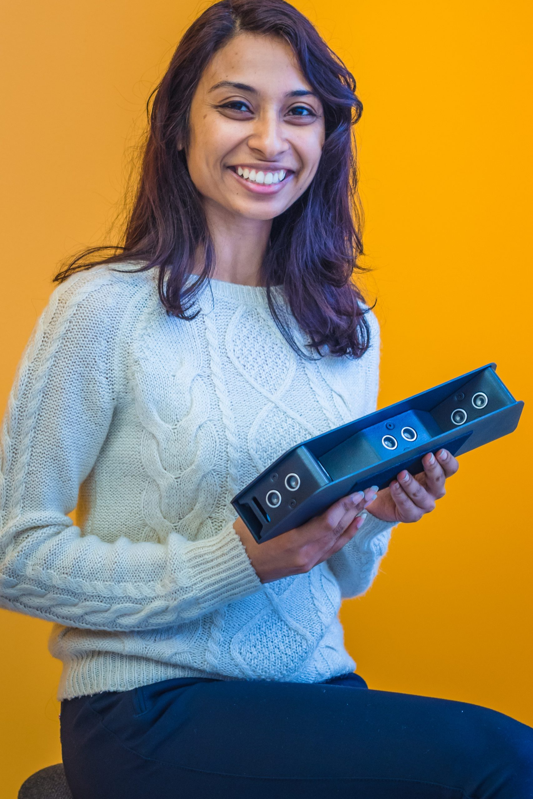 Photo of Pooja holding the Braze Mobility Sentina Max sensors