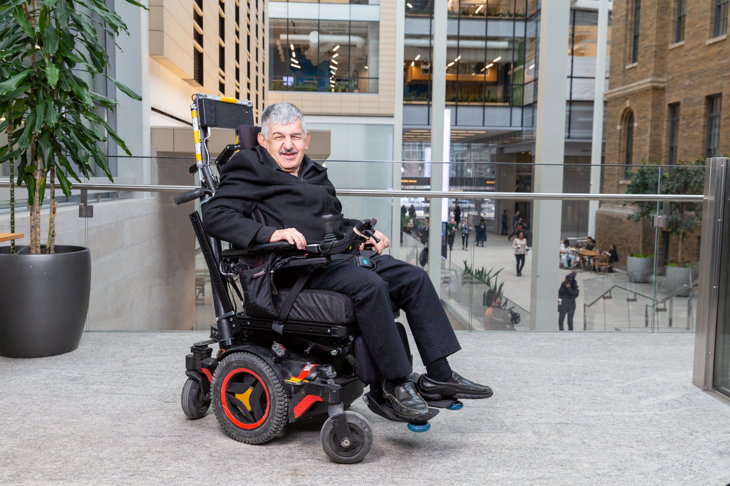 Photo of Hassan in a power wheelchair, a customer using the Braze Mobility product