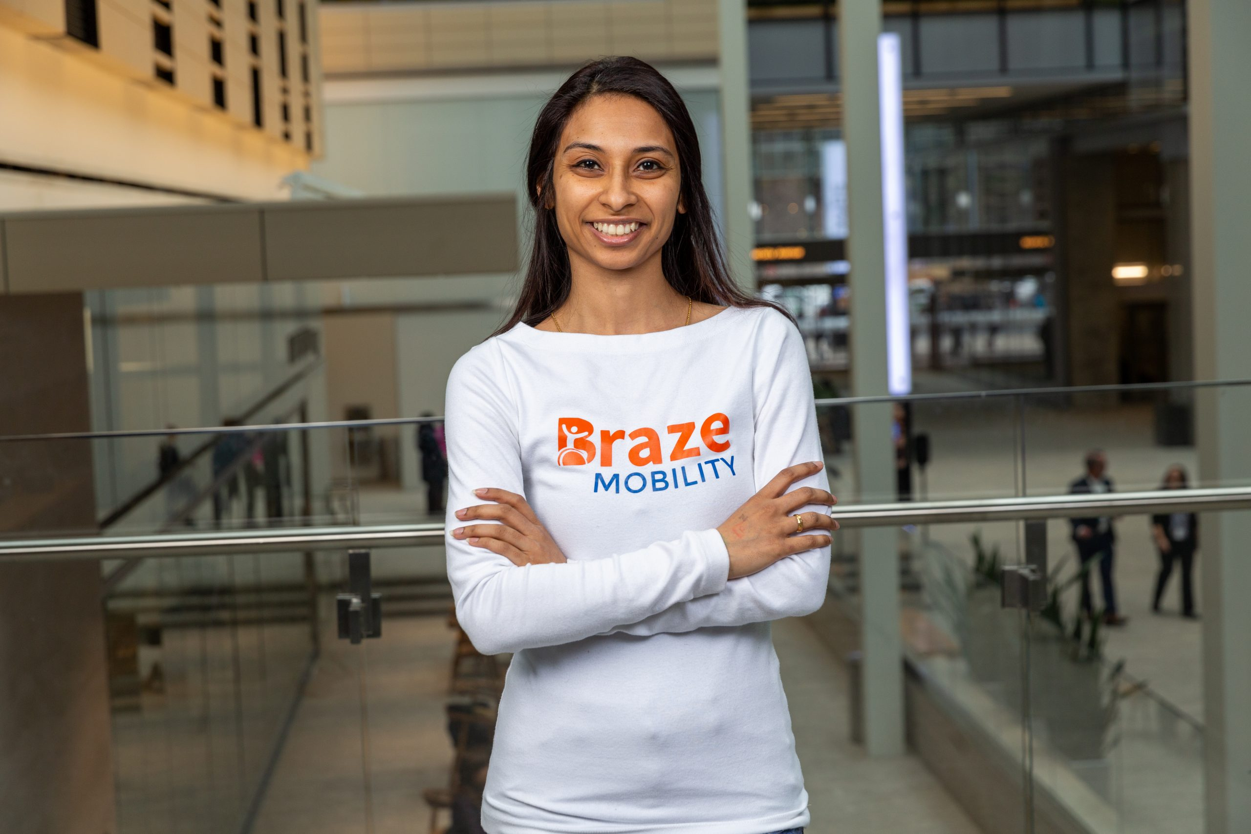 Photo of Pooja smiling with arms crossed wearing a white Braze Mobility long sleeved shirt
