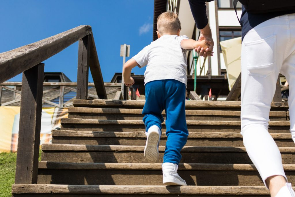 A young boy holding the hand of a woman, going up stairs