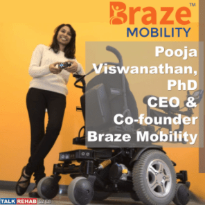 Photo of Pooja Viswanathan smiling and standing beside a power wheelchair
