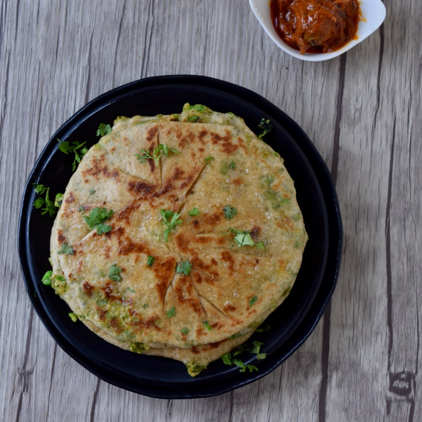 Delicious paneer peas paratha served with pickle