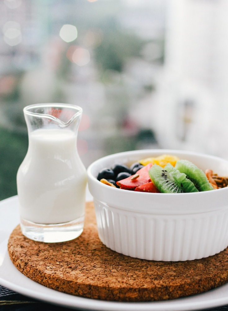 white bowl of fruit with a cup of milk