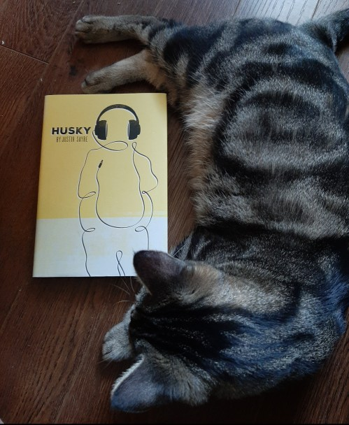 A book called Husky on the floor with a cat