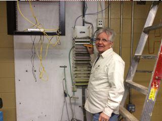 Pastor Tom Goss working on computer wiring