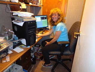 Lisa Goss sitting at the computer working on the website