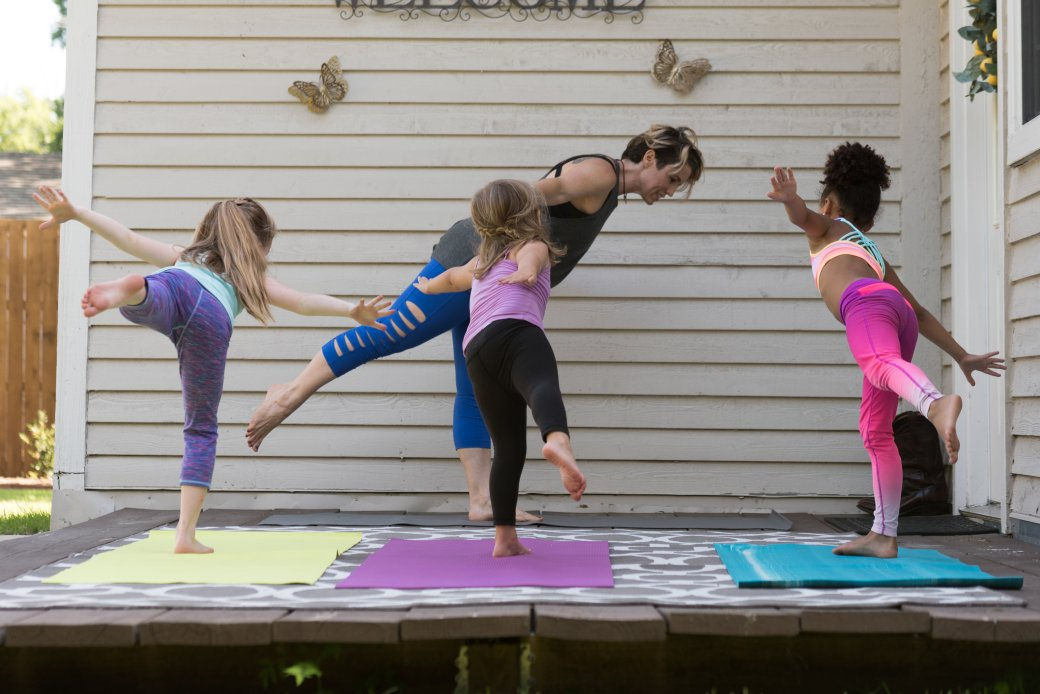 Kids yoga class outside in warrior 3 pose.