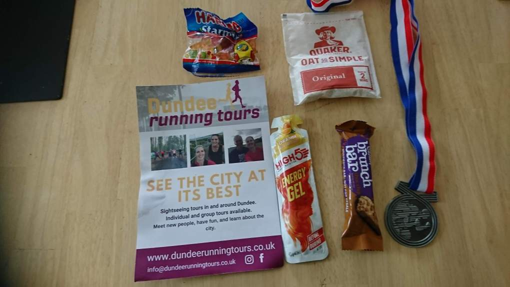 Photo shows the contents of the goody bag: Leaflet, Haribo, Oat So Simple, Brunch Bar and Medal