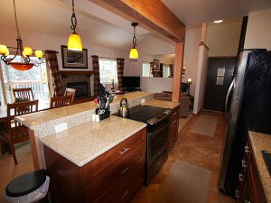 Fully equipped kitchen with bar seating for four is open to the dining room and living room.