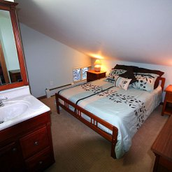 The second bedroom upstairs has a queen bed and half bath with hair dryer (before remodel).