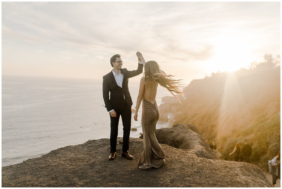couple on the cliffs at el matador beach taking engagement photos