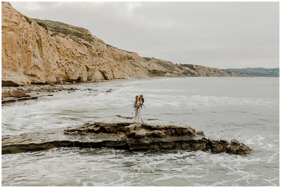 couple takes their elopement photos on torrey pines state beach