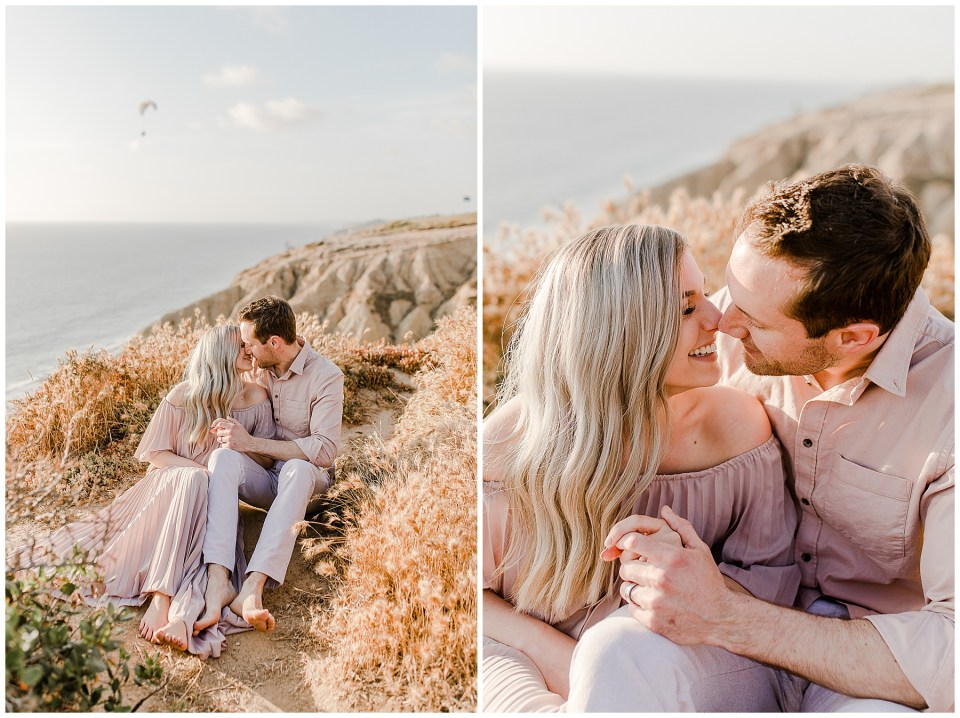 man and woman laughing and kissing while sitting near the cliff at torrey pines gliderport