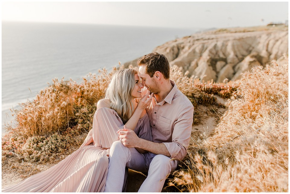 romantic engagement photos in la jolla. couple kissing on the cliff at torrey pines gliderport