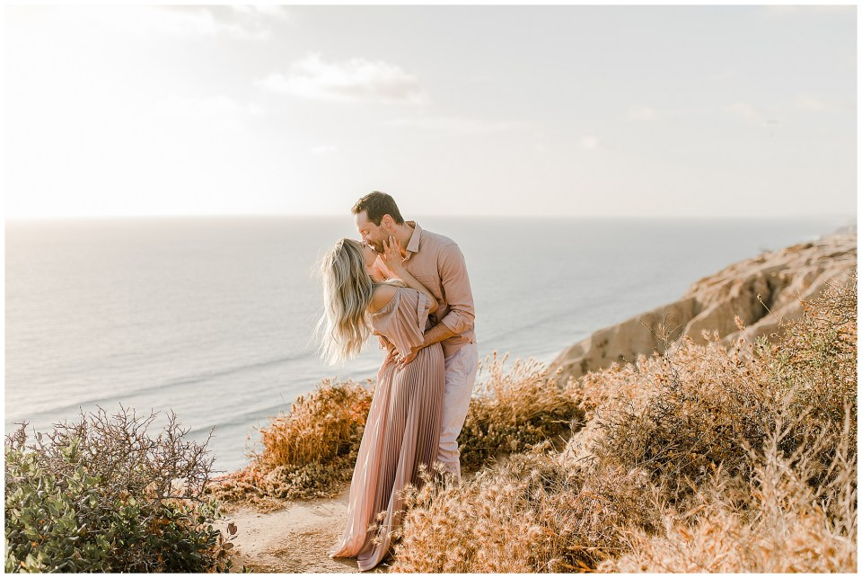 torrey pines gliderport engagement photos - couple kissing at the top of the cliffs in la jolla, CA