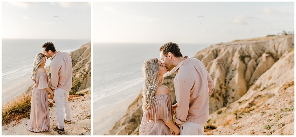 man kisses his fiance on her forehead during their engagement pictures at torrey pines beach in san diego, California