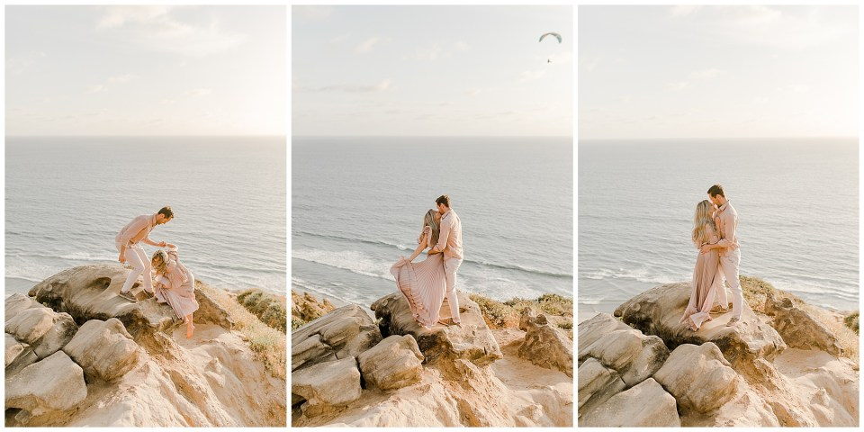 man and woman climb on a rock at torrey pines gliderport during their engagement photos