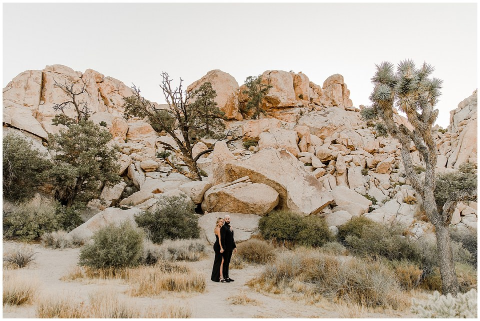 man and woman take dramatic portraits in joshua tree national park