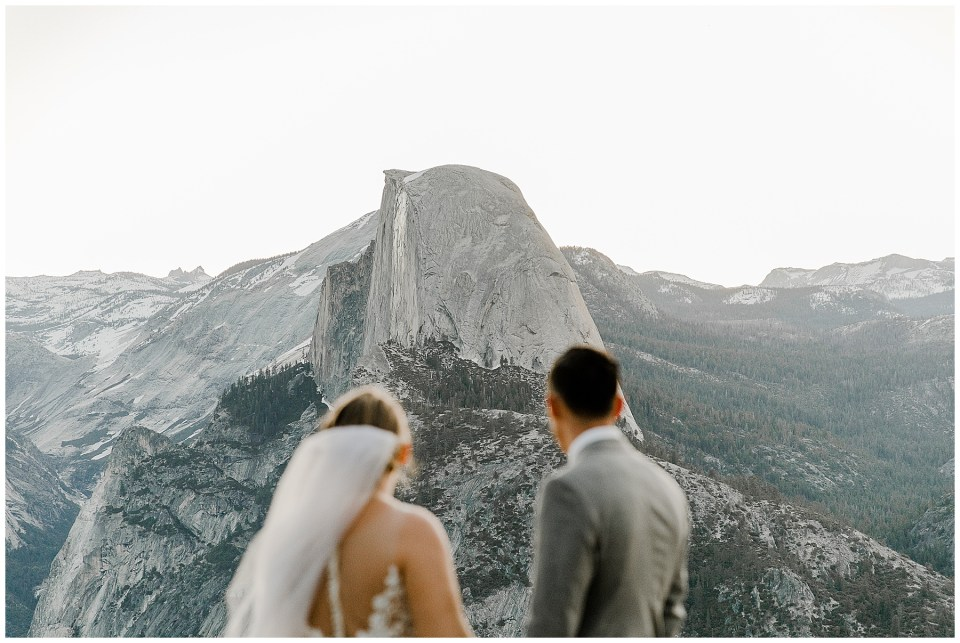 bride and groom looking at half dome