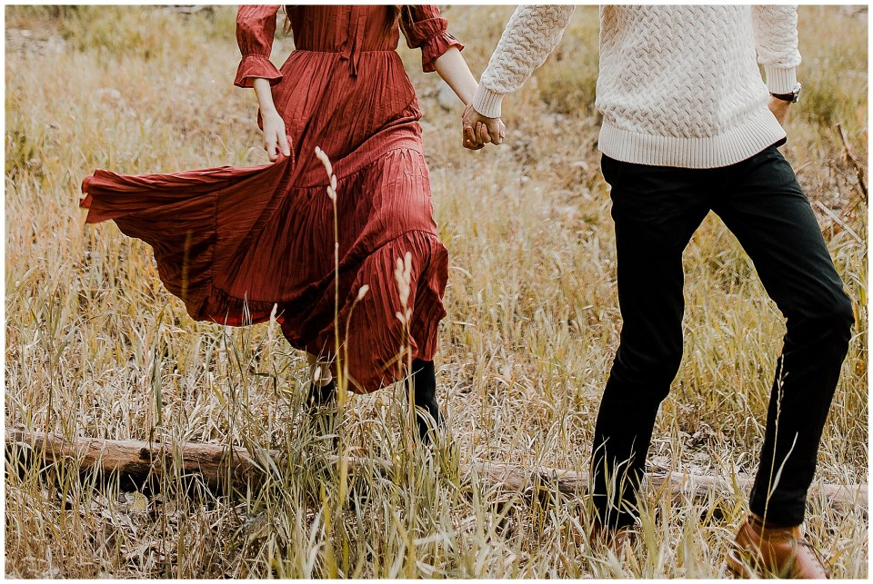 Couple holding hands and walking through the grass in their Big Cottonwood Canyon Engagement Session