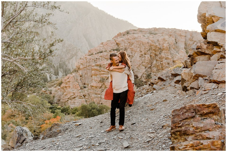 man is holding his woman while doing a piggy back ride in the mountains during their Big Cottonwood Canyon Engagement Session