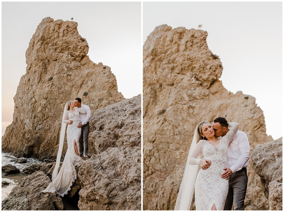 bride and groom climb on top of a rock in el matador beach