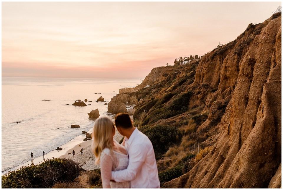 bride and groom look at the sunset at el matador beach