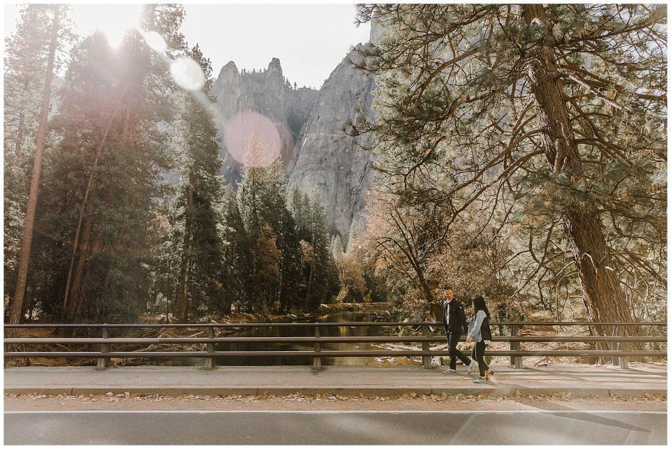 bride and groom holding hands walking during their adventurous yosemite engagement session