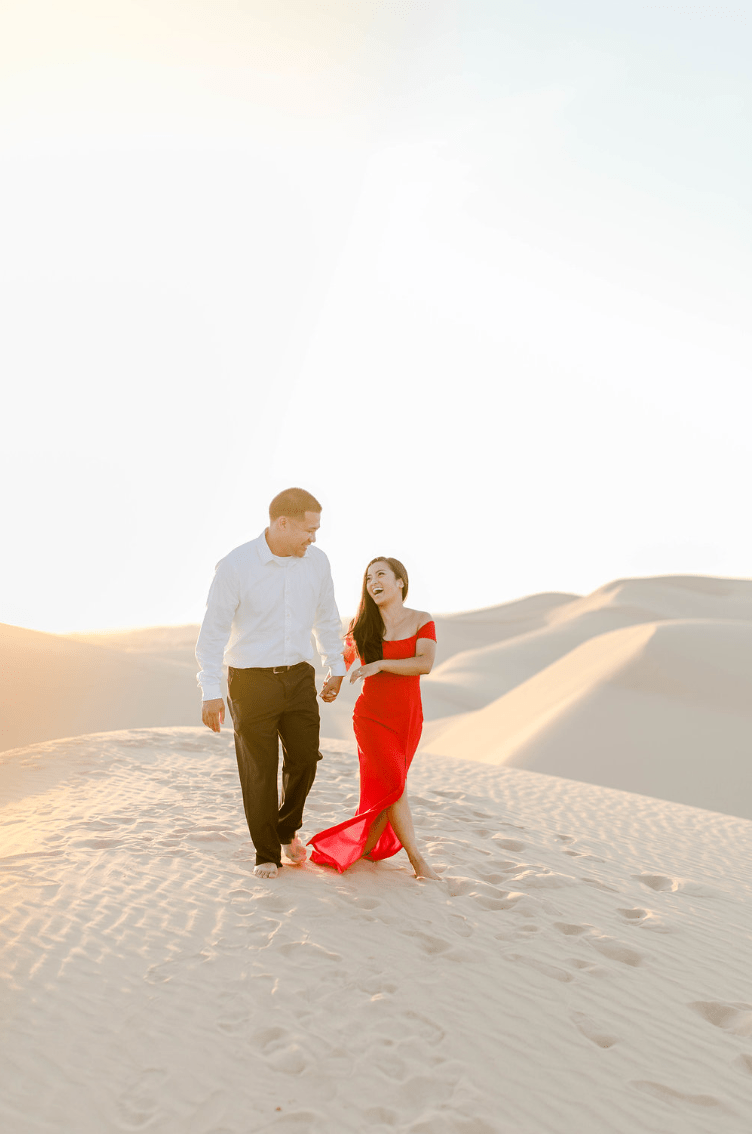man and woman holding hands and smiling during their adventure session in glamis sand dunes - Getting Instagram Worthy Photos in Glamis Sand Dunes