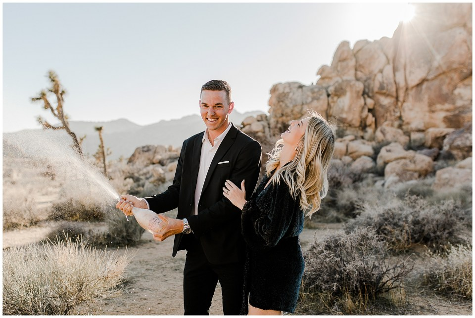 man and woman pop champagne during their joshua Tree National Park Engagement Photos