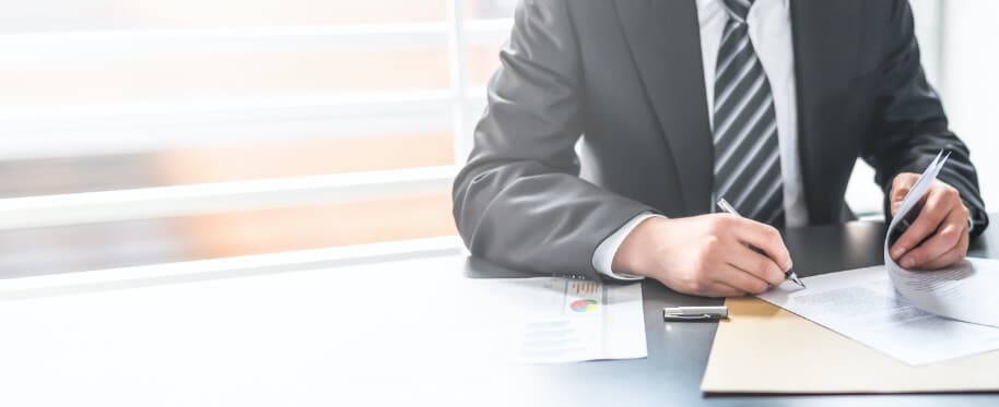 Man in a suit putting pen to paper