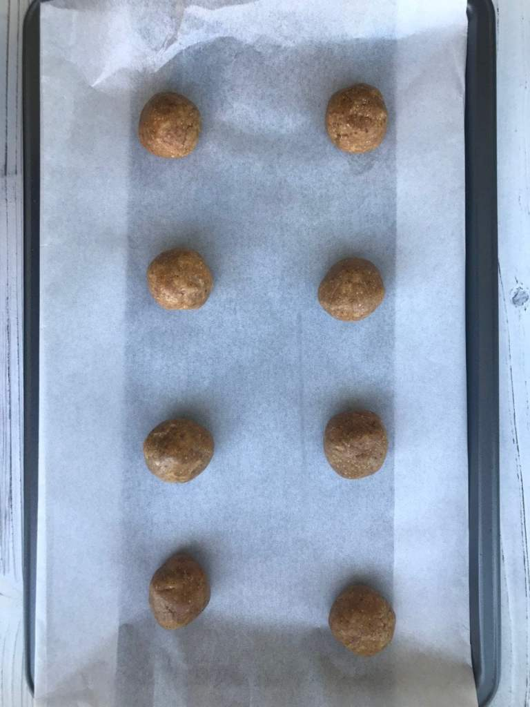 peanut butter cookie dough in balls on a baking sheet.
