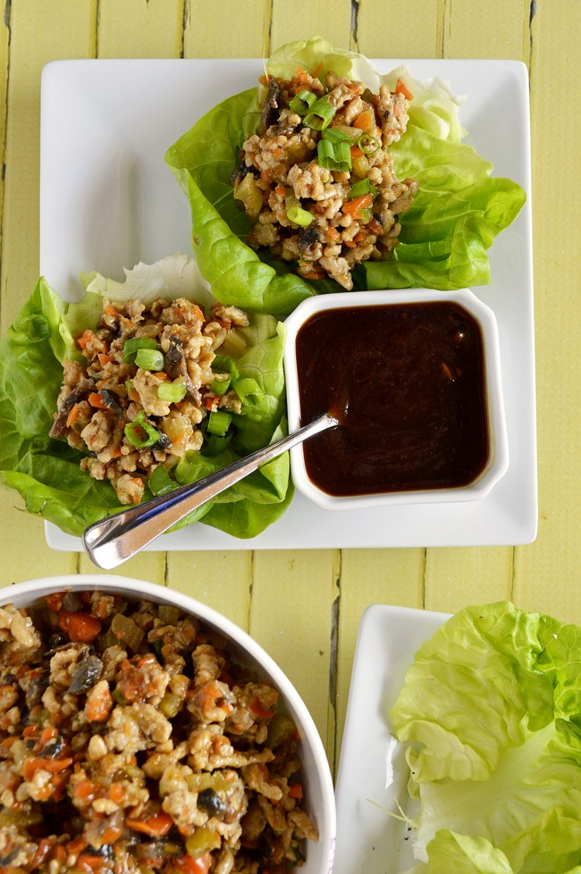 Gluten Free Chicken Teriyaki Lettuce Wraps sautéed with carrots, celery, mushrooms and green onions. Tossed with a sweet and salty teriyaki glaze and served in a bed of butter lettuce leaves.