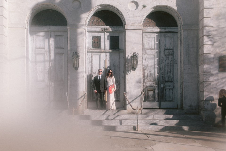 Couple stands in front of Marigny Opera House on their wedding day. Photo taken by New Orleans photographer Brei Olivier.