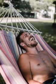 laughing man laying on hammock
