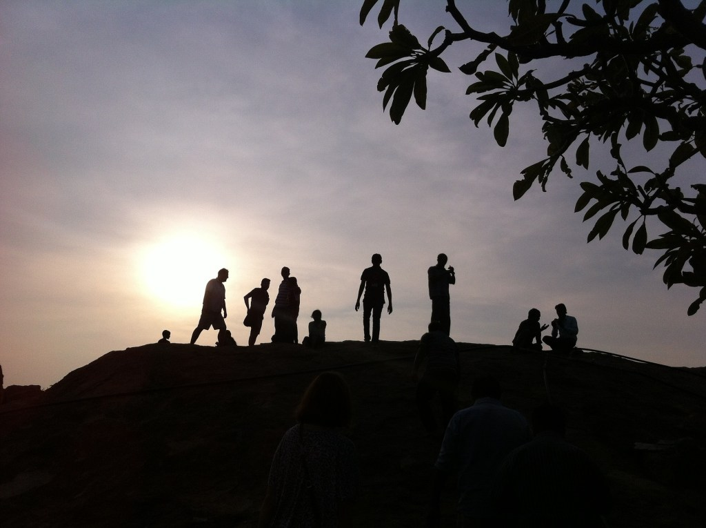 men in group on hill at sunset