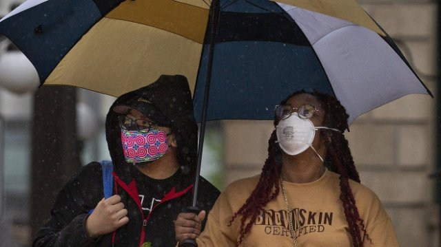 'Peter Vang and Tanaya Walker Vang of Shoreview take shelter from the rain on May 17 after shopping at the St. Paul Farmers' Market....' Christine T. Nguyen/MPR News