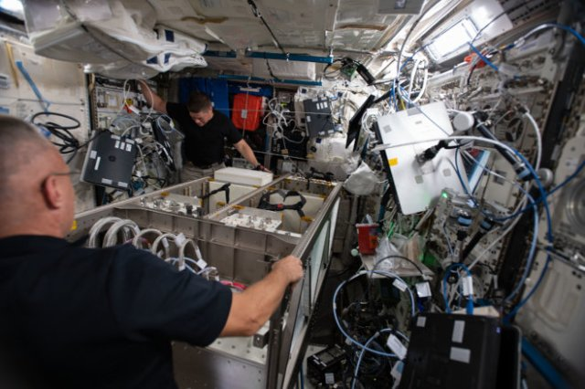 From NASA: Bob Behnken and Doug Hurley, installing a new European Drawer Rack Mark 2 in the ISS Columbus module.