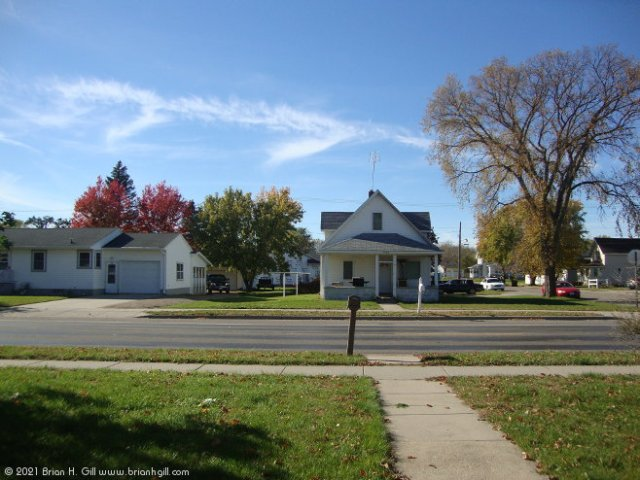 Looking across Ash Street South in Sauk Centre, Minnesota. Our front yard is green again, after the summer's drought. (October 25, 2021)