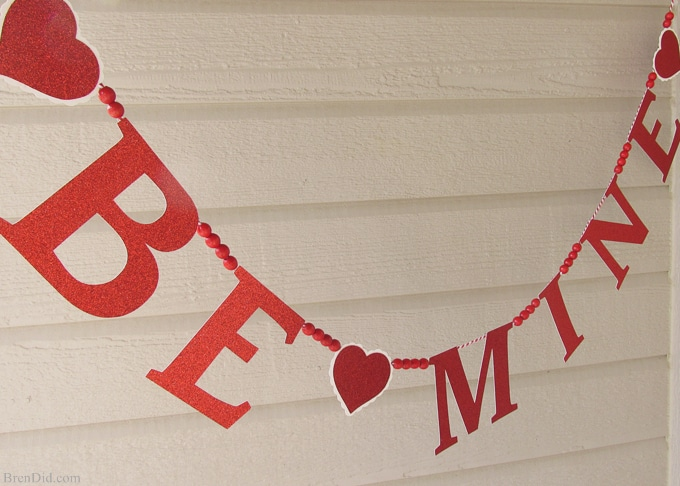 Get ready for Valentine's Day parties and events with this glitter garland inspired by Pottery Barn Kids. This easy Knock Off DIY craft uses glitter cardstock, some twine, and wooden beads to make a charming Valentine's Day banner for under $3.