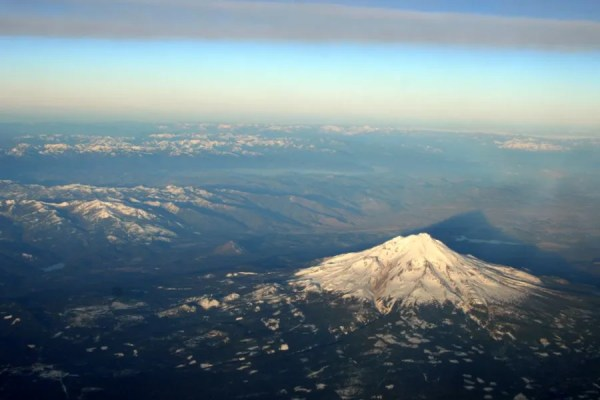 Mount Shasta casts a shadow with Black Butte visible behind and to the left