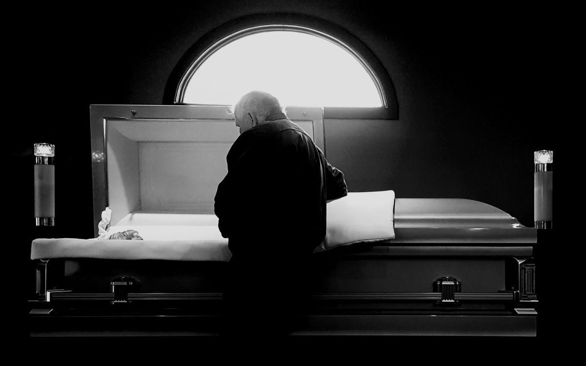 By a casket still