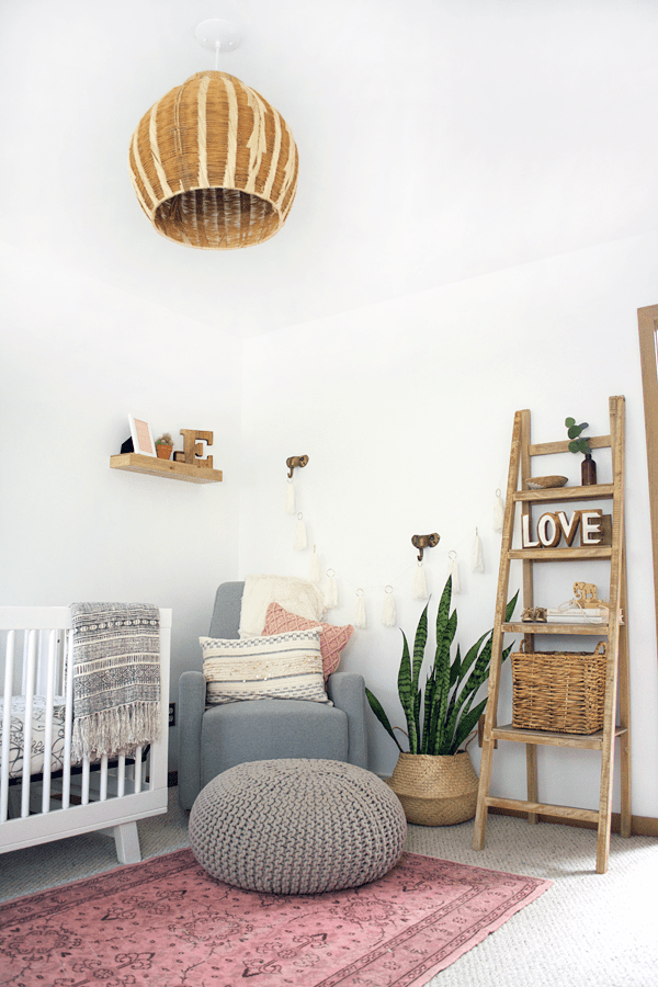 a boho girl's nursery with a pink vintage rug