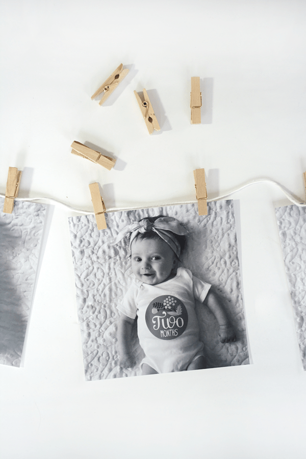 monthly baby photos hanging on string with mini clothespins