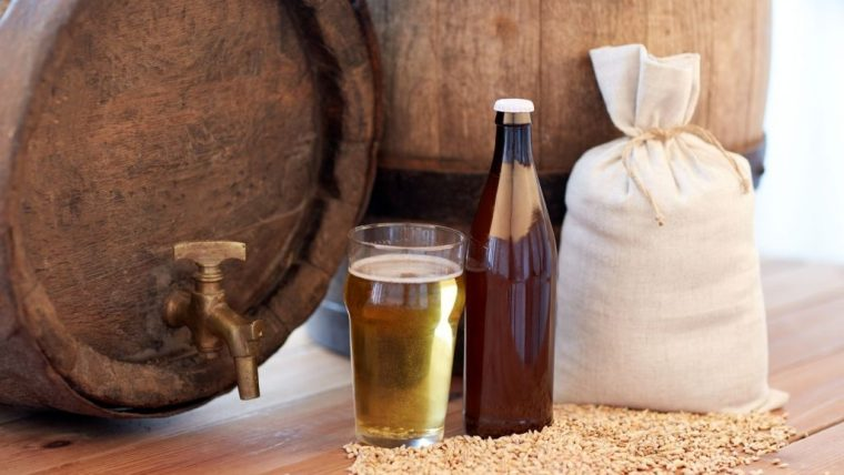 Wooden barrel, sack of grains and a glass of beer