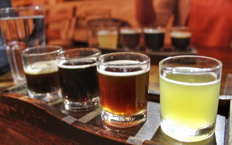 Beer tasting set up with 4 beer samples on a wooden plate