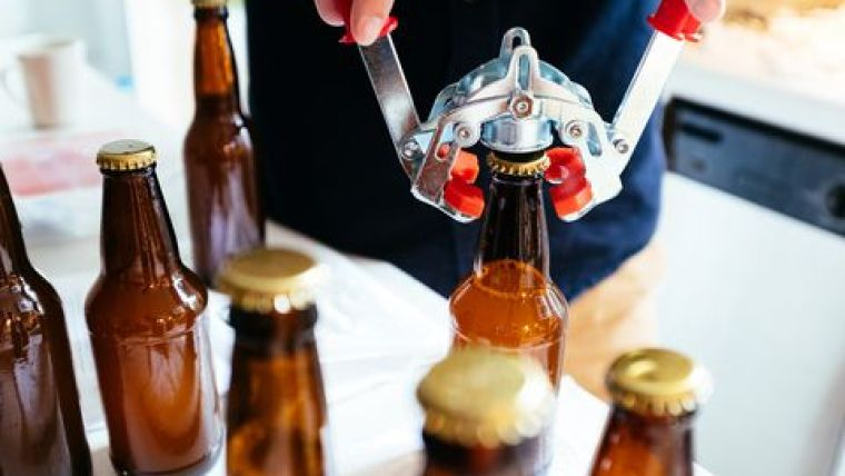 A brewer capping out beer bottles.