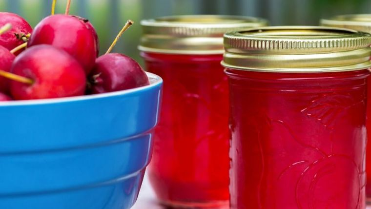 A bowl of cherries and jars of cherry jam.